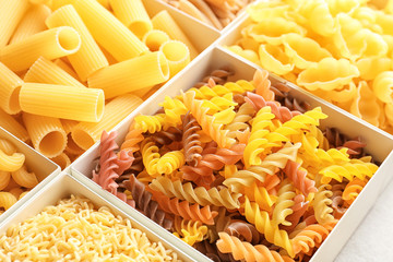 Boxes with different uncooked pasta, closeup