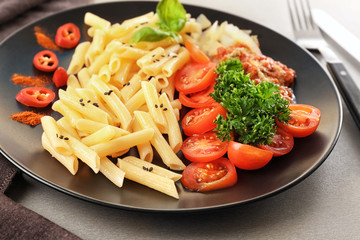 Plate of delicious pasta with bolognese sauce and tomatoes on table, closeup