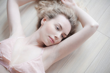 Young pretty woman in gentle lingerie lying on the floor. Beauty close up portrait of female face with natural skin, no makeup.