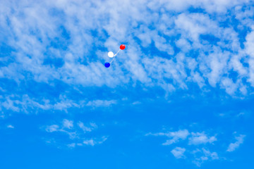 Colored balloons in blue sky with clouds, landscape