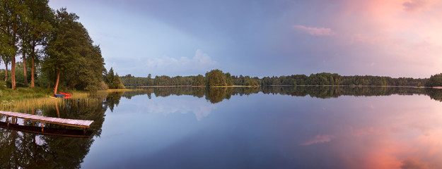 Tranquil water sunset reflections. / Lake with beautiful nature scenics panorama in north Poland.