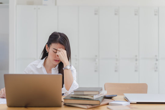 Stressed asian young business woman working with laptop and holding head with hands looking down. Negative human emotion facial expression feelings.