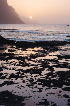 Cape Verde sunset at the rocky beach of Santo Antao Island. Mountains at the ocean
