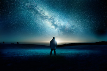 Photo sur Plexiglas Bleu vert A man stands watching with wonder and amazement as the moon and milky way galaxy fill the night sky. Night time landscape. Photo composite.