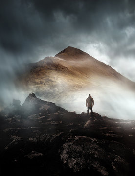 A person hiking looks onwards at a mountain shrouded in mist and clouds with the peak visible. Scenic landscape photo composite.