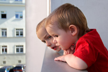 Gefahr: Kinder auf dem Balkon lehnen sich über die Brüstung