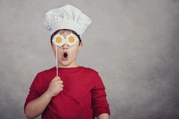niño gracioso con huevos fritos en sus ojos