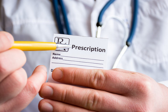 Doctor in foreground holding sample of prescription or recipe for drug, other hand indicates designation of prescription medication, which means issuing medicines by pharmacist only on prescription
