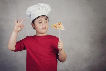niño cocinero gracioso con un trozo pizza