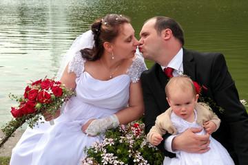 Junges Brautppaar mit Baby sitzt am See und küsst sich