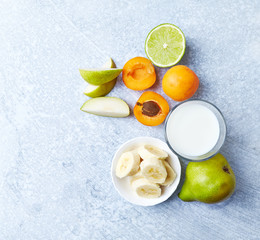 Fresh Ingredients for a Vegan Smoothie ( apricots, banana, pear, lime, mint and almond milk)