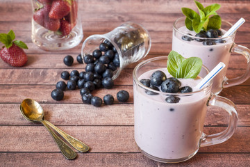 Blueberry yogurt in glass cups with fresh blueberries and mint on a wooden rustic table