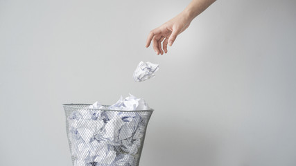 Woman hand throwing crumpled paper in basket