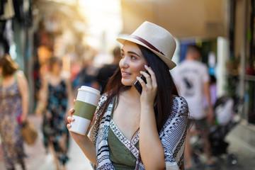 Junges Hipster Mädchen in der Stadt mit Mobiltelefon und Kaffee in der Hand