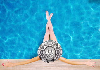 Girl with hat at the swimming pool. Concept of summer relax