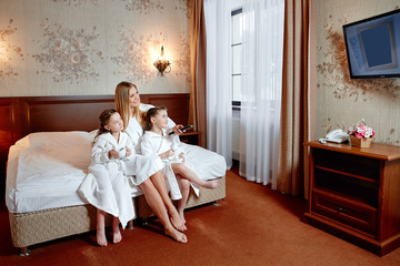 Happy family, mom and two twin girls watching TV. They're sitting on a bed in a hotel room.