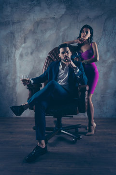 Portrait of rich gentleman in formal wear sitting in leather chair holding glass with cognac and cigar in hands, pretty charming lady in purple dress standing near isolated on grey background