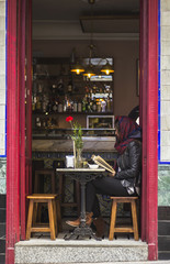 Woman reading book in Spanish bar with large open doors. Madrid city.