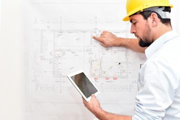 architect with tablet in front of a technical drawing - plan new building house // Bauleiter/ Architekt mit Tablet vor einer technischen Zeichnung - Plan Neubau Haus