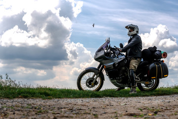 Rider Man and off road adventure motorcycles with side bags and equipment for long road trip, river and clouds on background, enduro travel touring concept
