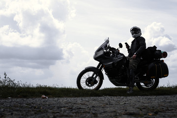 Biker man and tourist off road motorcycle with side bags, silhouette wallpaper concept, enduro advetnture, space for text, dark dramatic view