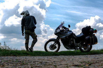 Biker man and tourist off road motorcycle with side bags Young man rider to rest during the trip to see the light of nature, silhouette wallpaper concept, enduro advetnture, space for text