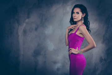 Portrait with copy space empty place of pretty stunning woman in cocktail dress holding hand on waist looking at camera isolated on grey background, advertisement concept