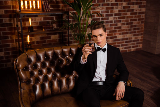 To you toast, manly, virile, harsh, stunning man in black suit with bowtie sitting on leather sofa over brick wall, holding glass with cognac in hand, looking at camera
