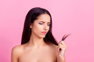 Nervous, frustrated, disappointed girl with naked shoulders looking at split ends of her dark hair with unpleased expression isolated over pink background