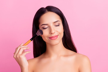 Sensual charming pretty woman applying blusher on her cheekbones using make-up brush with close eyes isolated over pink background