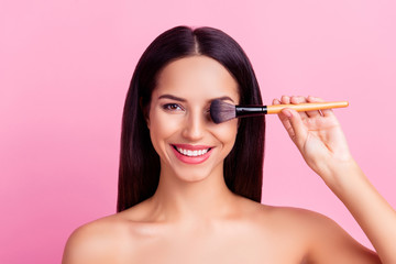 Funny, foolish, comic, charming, nice, cute girl with naked shoulders holding make up brush on eye place isolated over pink background