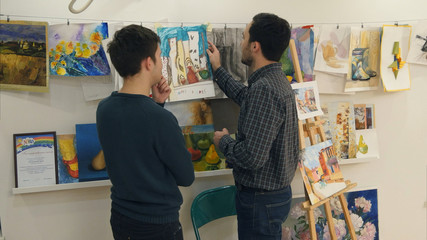Two young men discussing paintings drawn by art students