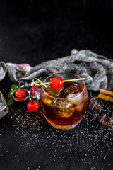 Glass of whiskey with ice and cherry on black background