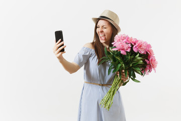 Young woman in blue dress, hat holding bouquet of beautiful pink peonies flowers, doing selfie on mobile phone isolated on white background. St. Valentine's, International Women's Day holiday concept.