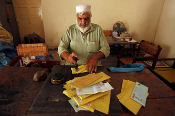 A postman stamps envelopes before delivering them, at the General Post Office in Peshawar