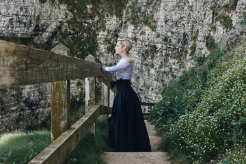 elegant girl posing on stairs with wooden railings on rocky cliff, Etretat, Normandy, France