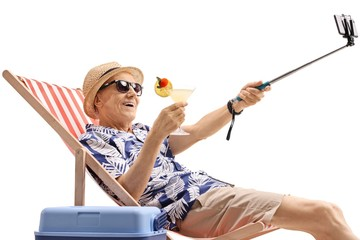 Elderly tourist with a cocktail sitting in a deck chair and taking a selfie with a stick