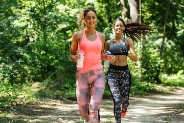 Two young woman  jogging outdoor on dirt road at the park .Green environment.