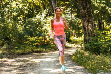 Young woman  jogging outdoor on dirt road at the park .Green environment.