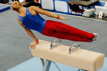 sports gymnastics athlete gymnast exercises on pomme horse