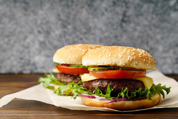 Classical burger with grilled meat, tomatoes, cheese, onion, cucumber and lettuce served on wooden table