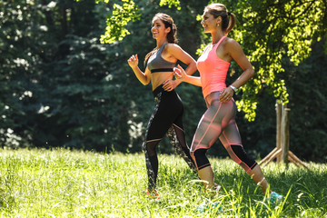 Two young female friends jogging at the woods.Green environment.