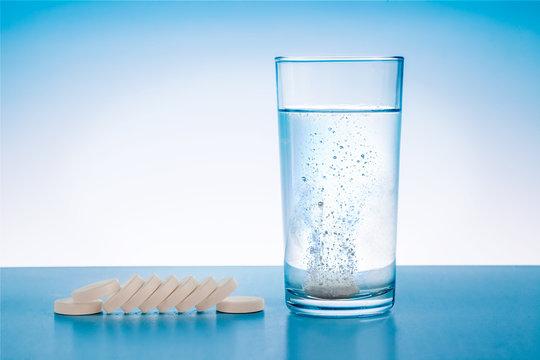 Wasserglas mit sprudelnder Tablette und Tabletten neben dem Glas