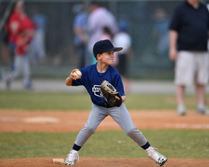 Young boy pitching the ball in a baseball game