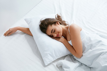 Pillows. Woman Resting On White Pillow Sleeping In Bed Wall mural