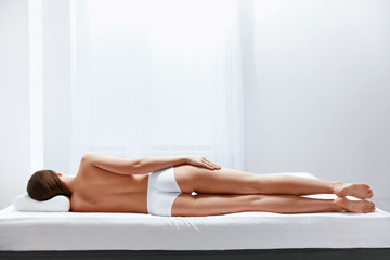 Orthopedic Mattress. Back View Of Woman Lying On Bed