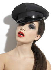 BRUNETTE WOMAN WITH RED LIPS SMOKEY EYES AND GLAMOUROUS POLICE HAT