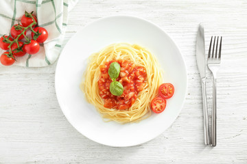 Plate of delicious pasta with tomato sauce on white wooden table