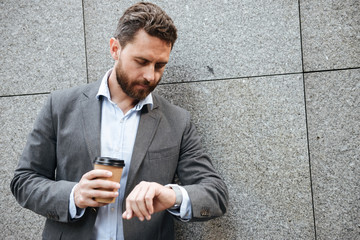 Photo closeup of adult businessman in gray suit and white shirt standing against granite wall, and looking at wrist watch while drinking takeaway coffee