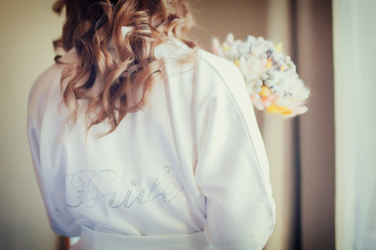 Bride's morning, woman wearing silk dressing gown.